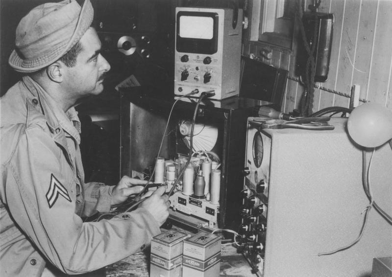 Sergeant Mickey Balsam, a radio repairman of the 50th Fighter Control Squadron, 4th Fighter Group, at work. Handwritten caption on reverse: '4FG, 50th Ftr. Control Sqdn, Radio Repairman Mickey Balsam, Author of song