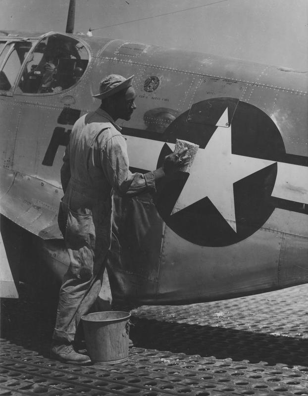 Staff Sergeant William Accoo of the 15th Air Force cleans a P-51 Mustang. Printed caption on reverse is damage: 'BIPPA, EA 35888. U.S. Mustang Flyers At Italian Base. Staff Sergeant William Accoo of Salen[sic], New Jersey, crew chief in a Negro group of the 15th U.S. Air Force, washes down the PP-51 Mustang fighter plane of his pilot with soap and water... to give it more speed. Mediterranean... Forces Photo PRO-HQ-44-2384. Serviced... London OWI (Inner... Certified... Passed by SHAEF Censor....' Printed caption also attached to reverse: '(CCU Photo). Competition is great among individual crew chiefs of the all Negro P-51 Mustang Fighter Group of the 15th Air Force in Italy, and it's never more evident than in this picture which shows S/Sgt. Wm. Accoo, 358 Keasby St., Salem, N.J., washing his plane down with soap and water. After this he will wax it.' On reverse: Mediterranean Allied Air Forces Photo and Crown Copyright [Stamps].