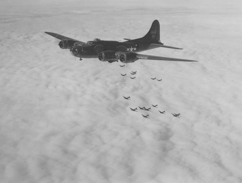 A 305th Bomb Group B-17 Flying Fortress (serial number 42-3412) flies above and ahead of a formation of B-17 Flying Fortresses. Handwritten caption on reverse: 'Faultless II.' On reverse: Photo By 8th AAF Combat Camera Unit [Stamp].
