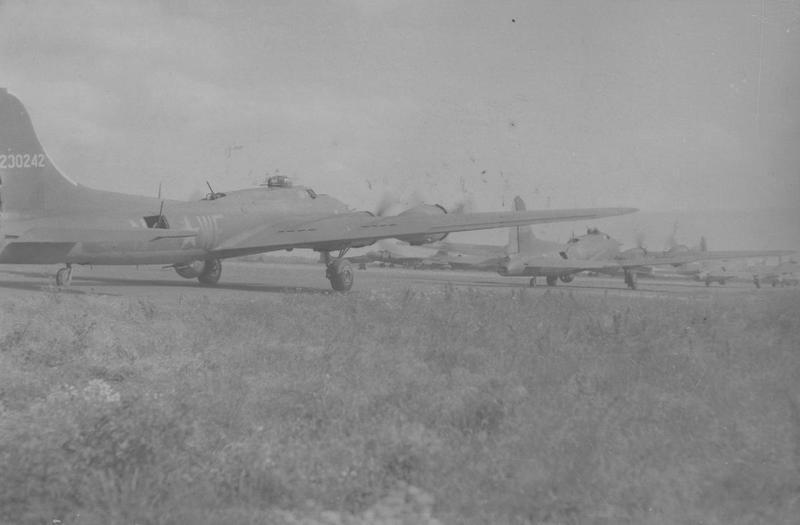 A line of 305th Bomb Group B-17 Flying Fortress taxiing at Chelveston airfield preparing to take off on another raid. The two rear-most B-17 Flying Fortresses belong to the 364th Bomb Squadron, (WF-N, serial number 42-30242) on the left and (WF-O, serial number 42-29807) on the right. Passed for publication 4 Jul 1943. Handwritten caption on reverse: '29/6/43. WF:N. WF:O 229807.' Printed caption on reverse: 'At A Flying Fortresses Base In Britain. This series of pictures shows scenes at a U.S. air base in Britain where Flying Fortresses are repaired, the scars torn in their sides - the price of victorious combats - patched up, engines overhauled and the planes made fit and ready for next bomb missions. U.S. Pool/F. Keystone (SG).' Censor no: 272762. On reverse: Keystone Press, US Army Press Censor ETO and US Army General Section Press & Censorship Bureau [Stamps].