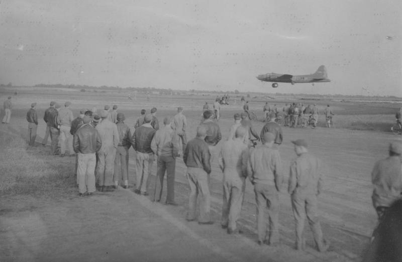 Ground crews of 305th Bomb Group B-17 Flying Fortresses wait for their aircraft to return to Chelveston airbase after a raid on the 30 June 1943; a B-17 Flying Fortress is coming in to land. Passed for publication 30 Jun 1943. Printed caption on reverse: 'At A Fortress Station In Britain. From an American base in Britain the Flying Fortresses carry out operational activities which result in terrible blows against the German industrial war machine. This series of pictures shows scenes at a Flying Fortresses station where hige[sic] bombers take off for the raids or return from their missions to be serviced by the ground crews, ready for the next raid. Keystone Photo Shows:-' Damaged printed caption also attached to reverse: 'Ground crews waiting for Flying Fortress [to?] return from a mission. [U.S.]Pool/F. Keystone (SS). 13-18.' Censor no: 272245. On reverse: US Army Press Censor ETO and US Army General Section Press & Censorship Bureau [Stamps].