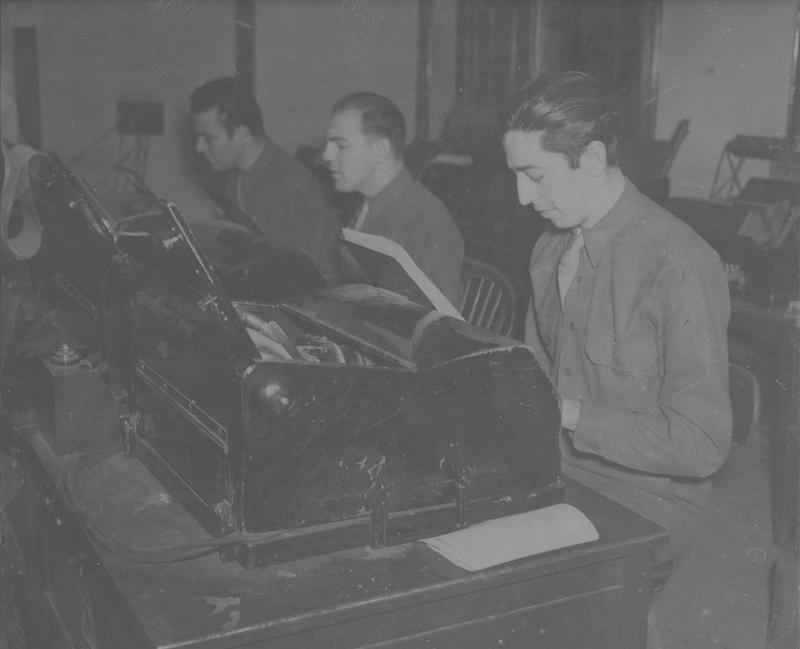 Private First Class William Archer uses a British-made teleprinter to send out field orders to USAAF Bomb Groups from Brampton Grange , the headquarters of the 1st Bomb Wing , 2 February 1943.   Handwritten caption on reverse: 'Teleprinter operators send out Field Orders, PFC William Archer uses a British machine at Brampton Grange, Station No. 103, HQ 1 Air Div.'  On reverse: US Army General Section Press & Censorship Bureau [Stamp]. Printed caption attached to reverse: Photo - 246568 Behind Scenes Pictures of U.S. Army Air Force Headquarters wing in England. (19 Pictures) Wide World Photo Shows: Working in Tele-printer room, right, is Private William archer, 1326, Webster Ave., N.Y.C. WW/ALA