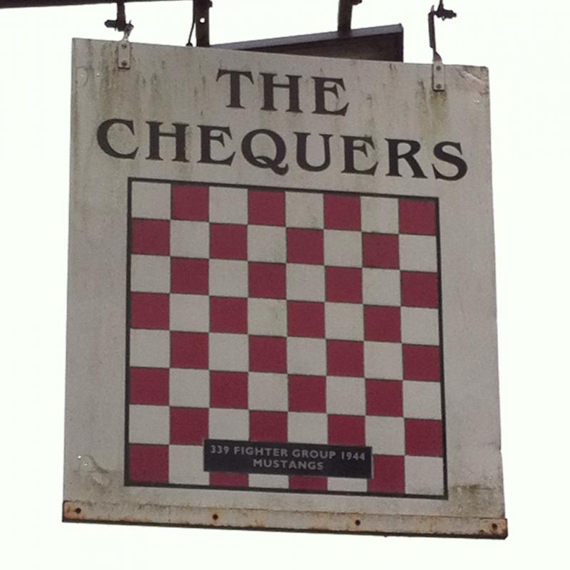 A photograph taken in January 2015 showing the sign of the Chequers pub in Fowlmere, Cambridgeshire. The sign is painted with red and white chequers on the one side to honour the American pilots of the 339th Fighter Group which were based at Fowlmere airfield from April 1944 to October 1945. The opposite side is painted blue and white chequers to honour the No.19 RAF Squadron which were also based at Fowlmere airfield prior to the arrival of the American airmen in 1944.