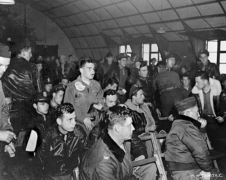 Briefing prior to the 491st Bombardment Group's first combat mission on 2 June 1944.  First row on the right is Lt. Col. Carl T. Goldenberg, 491st Group Commander. Second row on the left is Major Charles C. Parmele, 854th Squadron Commander. Third row near the center, wearing an officers cap and sheepskin jacket, is 1st Lt. James Carlin McKeown, pilot of the 853rd Squadron's Delirious Dolores (44-40200).