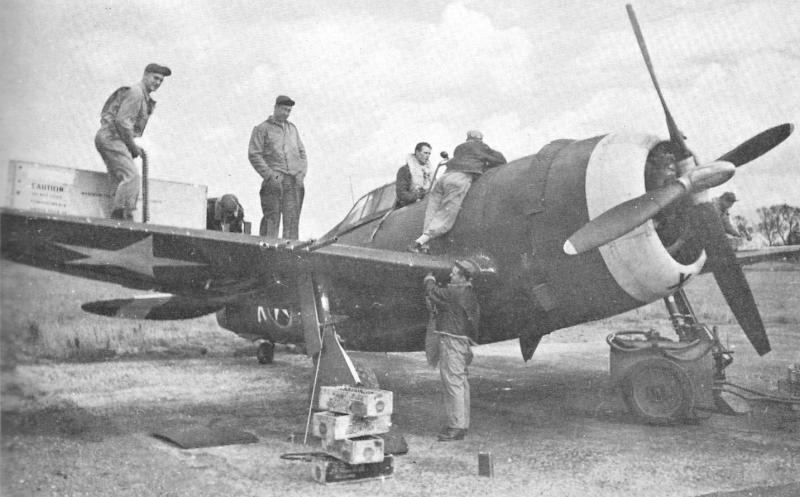 A typical post-flight scene at the 334th Fighter Squadron finds [then] Lt. William T. O'Regan in the cockpit of his P-47 Thunderbolt QP-X with his crew - L-R: Mike Traylinek, Dale Hall and Raymond H. Rames - all facing the camera (other crewmen are not known).