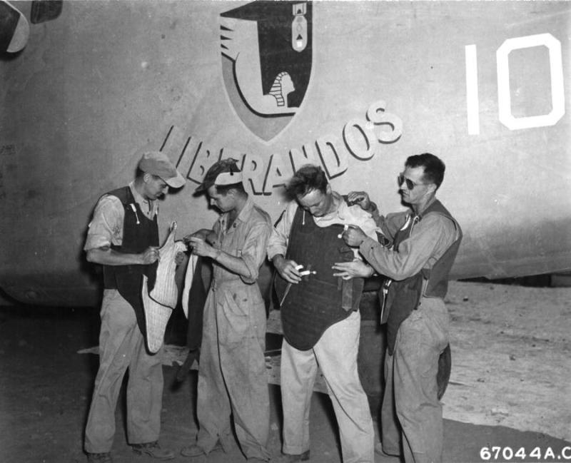 At an air base near Bengasi, Cirenaica, Libya, members of the 376th Bomb Group try on their newly issued