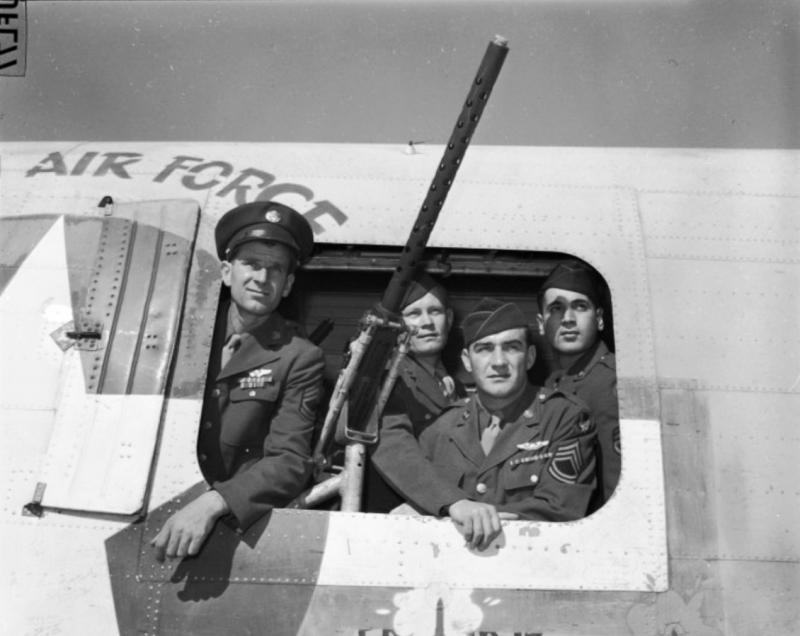 Four gunners who protected B-24D, 4111761, The Squaw,  on 35 of it's 71 missions. The gunners are looking out of the waist window of, The Squaw,  with a .50 Cal gun next to them. Left to right :   Sergeant Weir, Sergeant Givens, Sergeant Reilly, and Sergeant Guana.