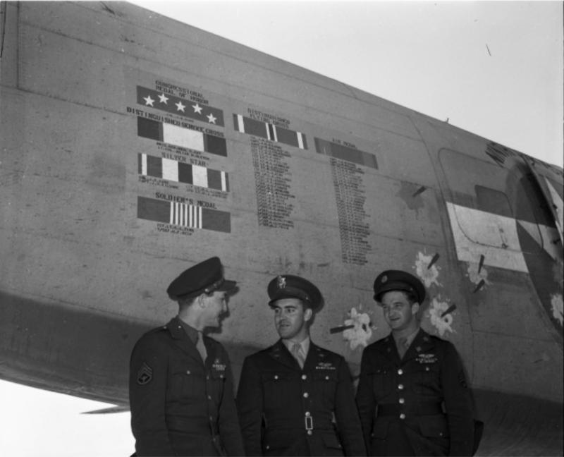 Image of three aviation crew members standing below the fuselage of the famous B-24 Liberator, #4111761