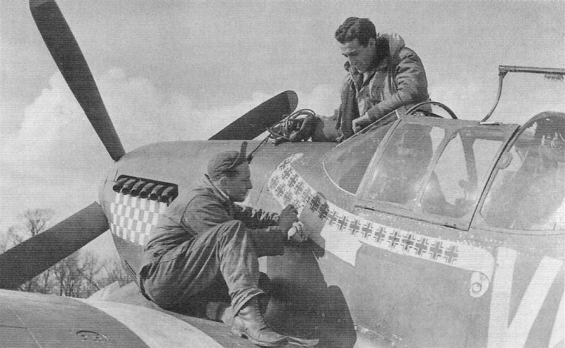 Fresh kill markings go on Don Gentile's P-51B Mustang 'Shangri-La', while he looks on. The sergeant painting them on is Dick Mansfield, Gentile's assistant crew chief. The chequerboard below the exhaust was a device created by Gentile and his wingman John Godfrey for quick identification in the air.