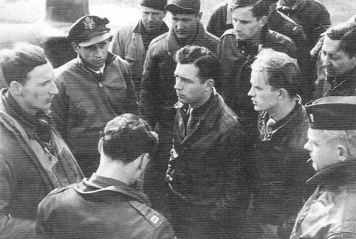 1944 - This last-minute briefing of 336th Fighter Squadron pilots includes Capt Kenneth D. Peterson (top left), 1st Lt Willard Millikan (left) and Capt James 'Goody' Goodson (back to camera).