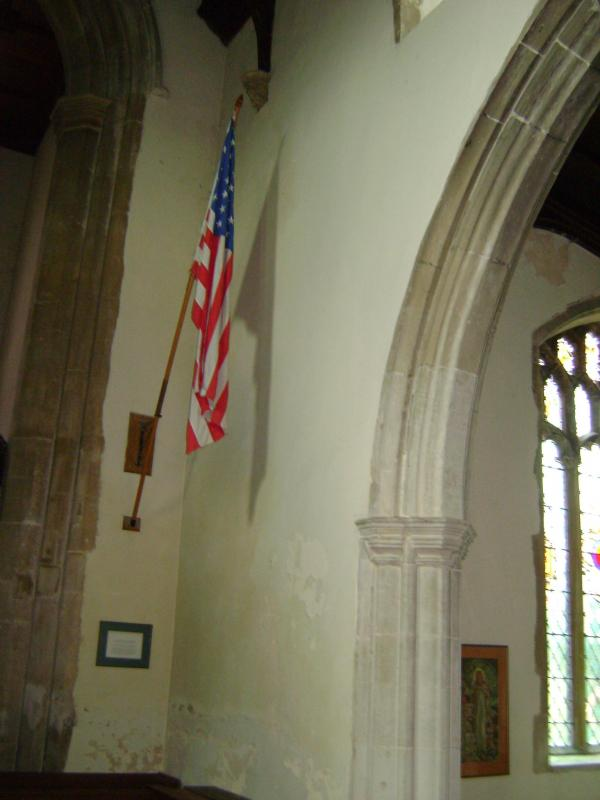 Transcript of the notice under the flag flying in the Parish Church of Stradbroke:  A flag similar to this was presented to the All Saint's Church, Stradbroke in August 1945 by the 95th Bomber Group, USAAF in grateful memory of their stay in the district during World War II and friendship between our two countries.  The original flag was stolen in January 1981 and was replaced through the kindness of the Commander of the USAF Base at Bentwaters and dedicated at a special service on All Saint's Day, 1st November, 1981.  The second flag suffered so severely from deterioration that, in 1991, it was considered necessary to replace it. Because a 48-star version of the United States flag was unobtainable and because it was considered that, in the interests of accuracy, a 48-star flag should be hung in this Suffolk Church, it was decided to make one in the village. The Parochial Church Council requested Alan Macnee, a resident of the village and, at that time Yeoman of Flags for Stradbroke Village, to make a replica of the flag so that it should be hung here. This flag was placed here in April 1992