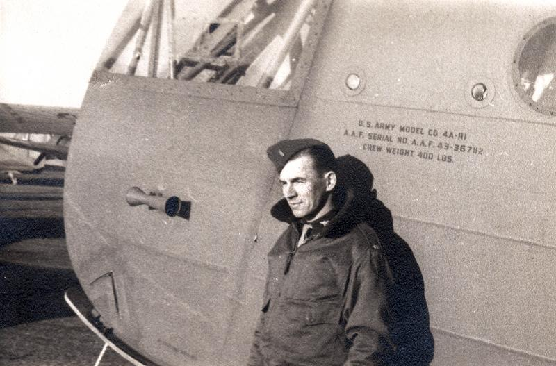 Flight Officer Eugene (Gene) M. Hock of the 316th Troop Carrier Group, stands next to a CG-4A glider, serial number 43-36782.