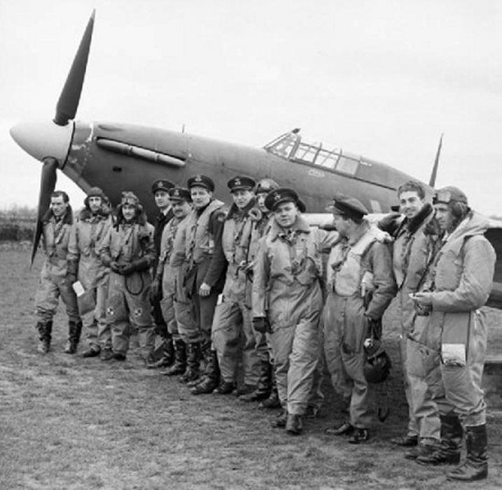 American pilots of No. 71 (Eagle) Squadron RAF gathered in front of one of their Hawker Hurricanes at Kirton-in-Lindsey, Lincolnshire, 17 March 1941. L to R:1.(83703) Charles Edward 'Ed' Bateman 2. (86619) William Henry 'Bill' Nichols – POW 3. +(84875) Stanley Michel 'Mike' Kolendorski 4. William Ervin G. 'Bill' Taylor 5. +(81621) Andrew B. 'Andy' Mamedoff 6. +(81622) Eugene Quimby 'Red' Tobin 7. (86617) Nathaniel 'Nat' Maranz 8. Luke Elbert Allen 9. +(83701) Kenneth Samson Taylor 10. Reginald Tongue (RAF) 11. (84657) Gregory Augustus Daymond – Fred Beaty 12. (87010) Sam Alfred Mauriello. IWM Photo - CH 2403.
