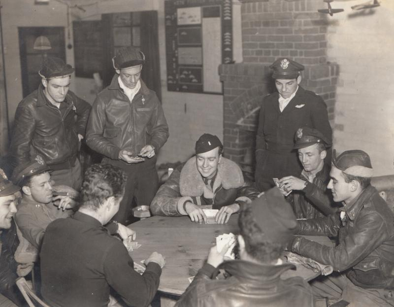 376th Fighter Squadron Pilots' Room. Card game with Maj. Roy B. Caviness Sqdn Commander (standing at the back). The game included Lt. Estel C. Alcorn, Lt. Clarence E. Sullivan, Lt. William D. Butler, Lt. John D. Duncan, Lt. Jimmie C. Wright, Capt. Roswell Freedman, Capt. James B. Cheney and Capt. James Hall. Museum object reference no. BAM_0026