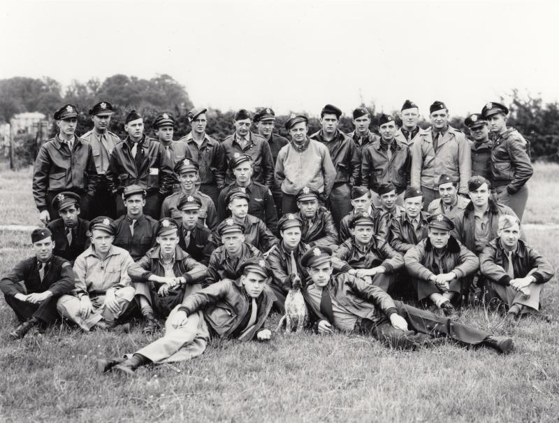 375th Fighter Squadron, 361st Fighter Group. Bottisham, mid-July 1944.   Left to right, back row:  Howard Spaulding, Herbert Boelter, David Morgan, James Eason, Murray Bell, Eugene Cole, David Edwards, William Shackelford, William Kemp, William McCoppin, Maynard Emlaw, Dustin Cowle, William Gill, Eugene Gentzler and Bruce Rowlett  Left to right, second row:  Charles Narvis and Joseph Kapr  Left to right, third row:  Raymond Comer, Alton Snyder, Robert Adams, Sherman Armsby, Robert Wright, Warren Ewert, John Black, Roswell Freedman (Squadron Commander), James Hall and Urban Drew  Left to right, fourth row:  James Donohue, William Rogers, John Thomas, Russell Sobieski, Merle Rainey, Dean Morehouse, Elroy Neely, Francis Glankler  Left to right, fifth row: Charles Cummins, 'Snitz' and Martin Johnson  Museum object reference no. BAM_0308