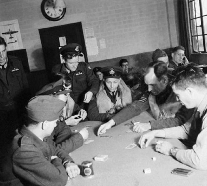 In the Pilots' Dispersal Hut at Rochford airfield, personnel of No 121 (Eagle) Squadron play Poker as they await the order to 'scramble'. Left to right they are: Pilot Officer Beatie (standing, from Georgia), Pilot Officer Heppel (New Jersey), Pilot Officer Kearney (New Mexico), Flight Sergeant Blanding (South Carolina), Flight Sergeant Carpenter (standing, from Pennsylvania), Flight Officer Hasey (Oklahoma), Flight Sergeant Sanders (Tennessee) and Flight Sergeant Fred Vance (Virginia). In the rear right-hand corner of the photograph, the telephonist can be seen, along with several other personnel awaiting the call to action. IWM Photo D 9514