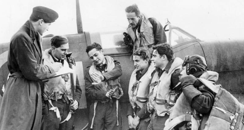 The Intelligence Officer at the headquarters of the second Eagle Squdron (121 Squadron), Sir Michael Duff-Assheton-Smith, takes notes as pilots describe their most recent sortie. They are, (L to R) Sq. Ldr. Powell; Pilot Officers W. James Daly, Hugh Kennard, Le Roy A. Skinner, Clarence Martin, and (standing on wing), R. Fuller Patterson.
