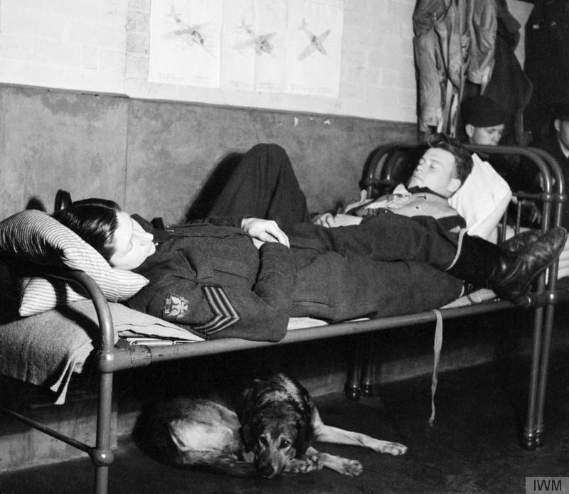 'Flight Sergeant Bill Kelly (left) and Flying Officer Osborne sleep between 'sweeps' in the Dispersal Hut at Rochford airfield. Underneath the bed on which they sleep is the station mascot, a dog called Roger. The original caption states that