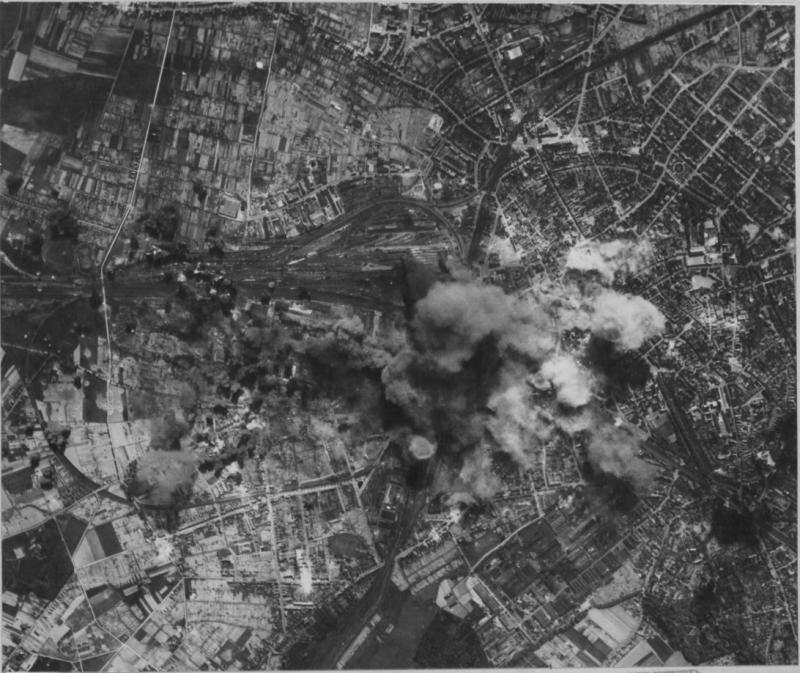 'Forts maul rail center -- Bombs from Boeing B-17 Flying Fortresses strike the marshalling yards at Osnabruck as US 8th AAF heavies attacked 13 May 44. Smoke from a nearby steel plant can be seen rising as the American bombs take their toll. Hits were also registered on the steel plant. 95th BG.' Photo from 42-107201