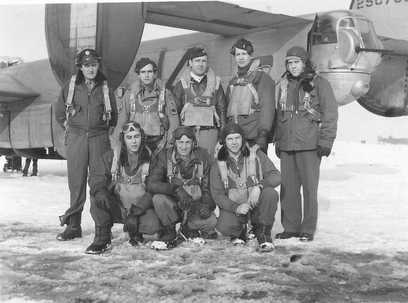 """Standing:   T/SGT Max K. Van Buren – FE; T/SGT Leon C. Huggard – RO; CPT Charles S. """"Sam"""" Evans – P; 1LT Frederick A. Johnson – CP; 1LT George F. Adkins – B Kneeling:  S/SGT James A. Michaelson – G; S/SGT Lawrence R. Matson – Armorer/WG; S/SGT Darrell W. Latch – G Missing:  2LT Walter M. Cline -- N; S/SGT Donald R. Conway -- FE  Winter 1944, Horsham St. Faith  The aircraft behind the crew is likely B-24J-5 FO, 42-50768, ARISE MY LOVE AND COME WITH ME.  If so, this photo would have been taken just after either mission no. 21 on 30 October 1944 to Hamburg or mission no. 22 on 5 November 1944 to Karlsruhe."""