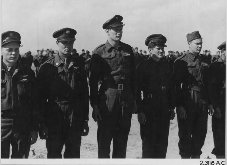 "Original USAAF photo caption :   ""Left to right : S/Sgt. Richard V. Fetroe, La Fayette Ind.; S/Sgt. Ralph F. Harms, Mt. Shasta, Calif.;T/Sgt. Chas. Kimtantes, Clarksville, Pa.; T/Sgt. Dell W. Kettering, Monmouth, Ill.; T/Sgt. Louis B. Kirkpatrick, Steelville, Mo. and S/Sgt Herschel H. Leist, Bocyrus, Mo., all of whom received Air Medals."" [ Sgt Leist is only partially shown at extreme right  - Awards ceremony in North Africa – photo sent on 3 March 1943 through Evaluation Unit, AAF from 9th Combat Camera Unit, Cairo, Egypt. ]