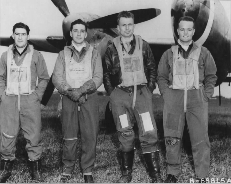 """Official USAAF photo B-66815 AC – Original caption : """"Lt. Colonel Johnson and other fighter pilots of the 20th Fighter Group in front of a Lockheed P-38 """"Lightning"""" at an air base in England"""
