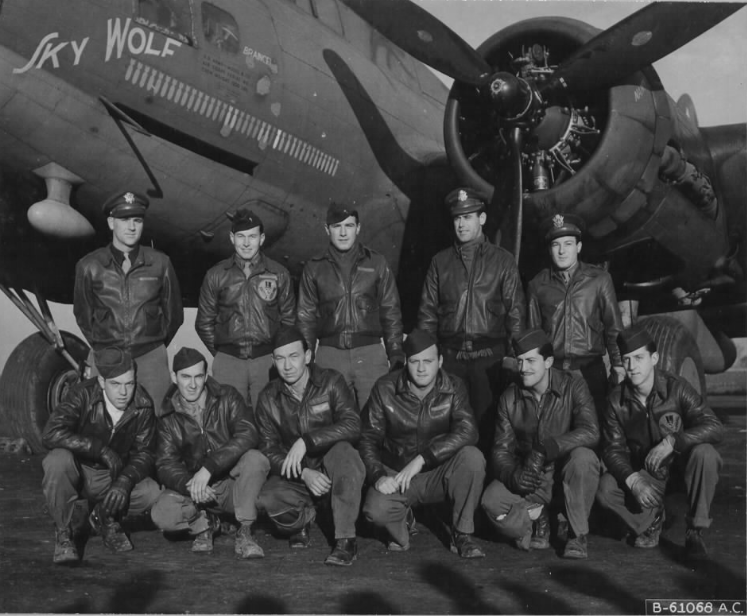 """Official USAAF photo B-61068 AC – Original caption : """"Lt. Kyse and crew of the 358th Bomb Squadron, 303rd Bomb Group, beside the Boeing Flying Fortress """"Sky Wolf"""". England, 11 November 1943.""""  [ Back row, from left ro right : 1st Lt Walter R. Kyse; 2nd Lt William C. DaShiell; 2nd Lt Hilton C. Mabie; 2nd Lt Thomas H. Sutherland; 2nd Lt Don J. De Laura / Front row, left to right : Sgt Arthur H. Robinson Jr; S/Sgt Bernard J. Radebaugh;  ] S/Sgt Robert L. Stevenson; Sgt Clifford M. McKinney, Sgt Robert J. Owen; Sgt George J. Morrison. ]"""