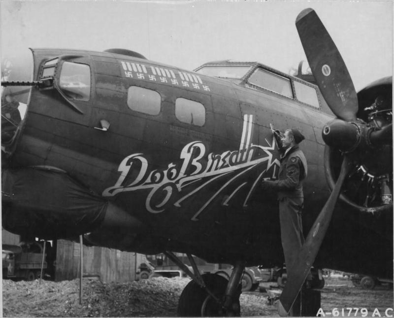 5 April 1944: Ball turret gunner SSGT Roland Clark of the 452nd Bomb Group touches up the nose art of