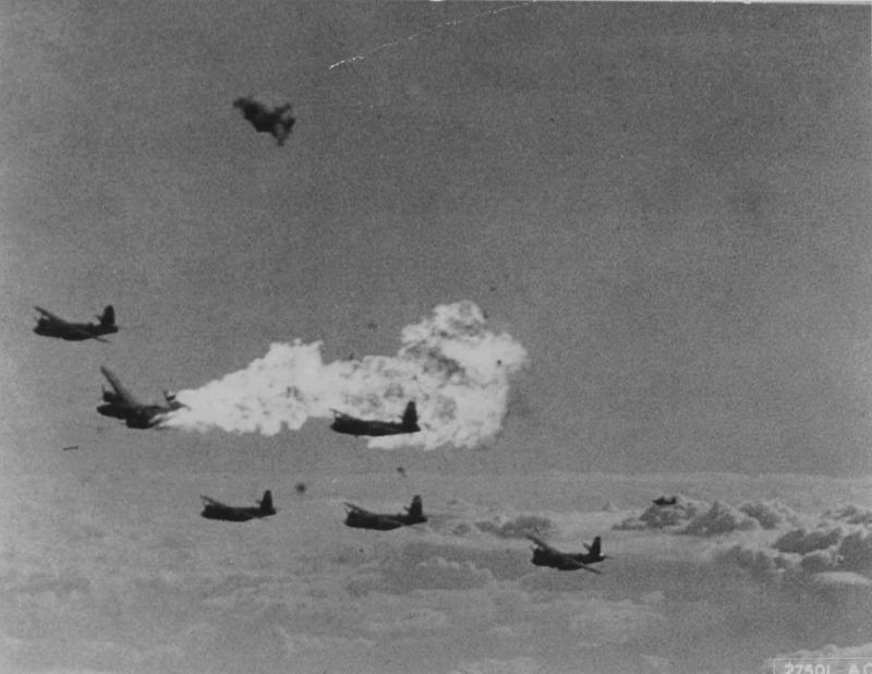 Flak Over Frevant - Flames and smoke are seen billowing from a Martin B-26B-30-MA Marauder, s/n 41-31884, unit marking YU-H, after receiving a direct hit from flak igniting fuel in the left wing tank. This aircraft impacted near Rebreuve-sur-Canche, France on 5 February 1944. K.I.A. were: Capt. James N. Bryan (P), 1LT. Salvatore E. Echo (Bombardier), 1Lt. William J. Hook (C-P), Capt. Charles L. Whyte (N), SSgt. John A. Holton (F-E/Gunner), SSgt. Silveo Tulipane (Gunner), and TSgt. William F. McLaren (Radio Operater).