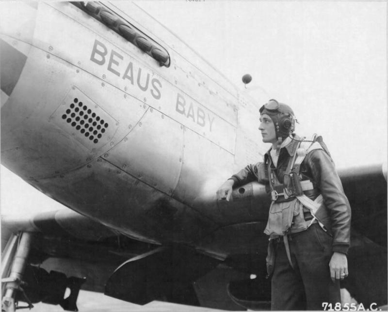 Lt Edward C Beaumont, pilot of the 364th Fighter Group, 67th Fighter Wing, looks up at the nickname of his North American P-51D 'Beau'S Baby' after returning from a mission, to the 8th Air Force station F-375, Honnington, England. 17 August 1944.