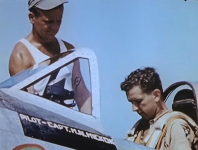 Captain Howard N. Hickok, 65th Squadron, 57th FIghter Group, being strapped into his P-47 cockpit by his crew chief just before a mission. Northern Italy.