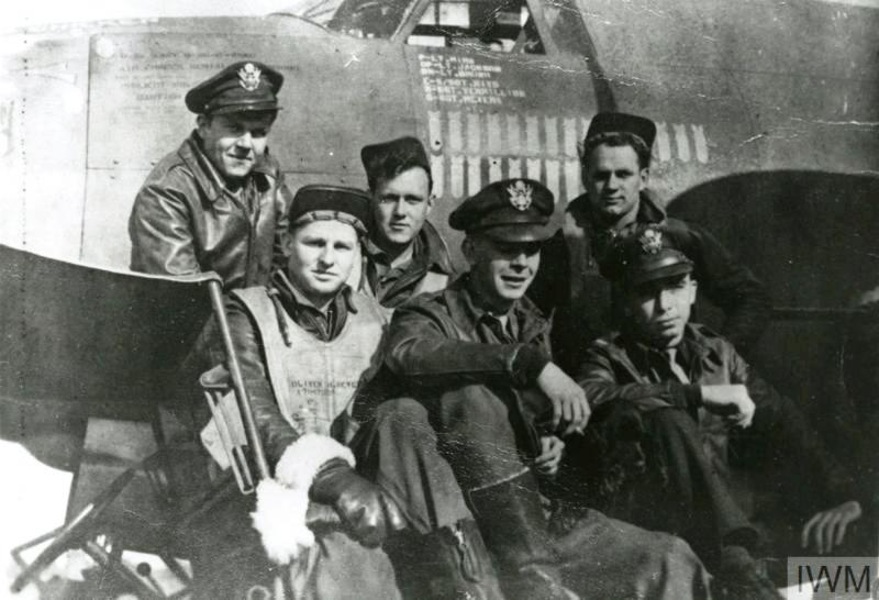 A bomber crew of the 323rd Bomb Group with their dog mascot