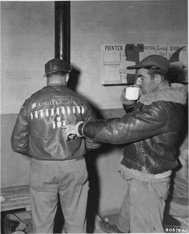 Warming up after a safe return from a raid on Norway, is S/Sgt. Frank C. Rumberger [ Johnston, Pa ], while S/Sgt. Peter Kucher [ Pittsburgh, Pa ], enjoys his coffee and admires Sgt. Rumberger's jacket. Both are crew members of the Boeing B-17 'Lucifer, Jr 42-29988