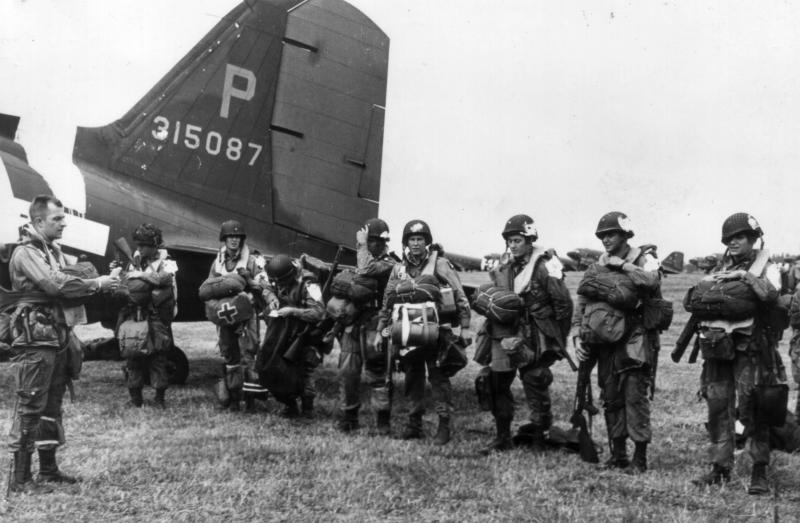 Paratroopers get final instructions before leaving on aircraft 43-15087, chalk #2, piloted by Capt. Matt J. Luoma of the 95th Troop Carrier Squadron, prior to departing for the D-Day drop on Normandy.