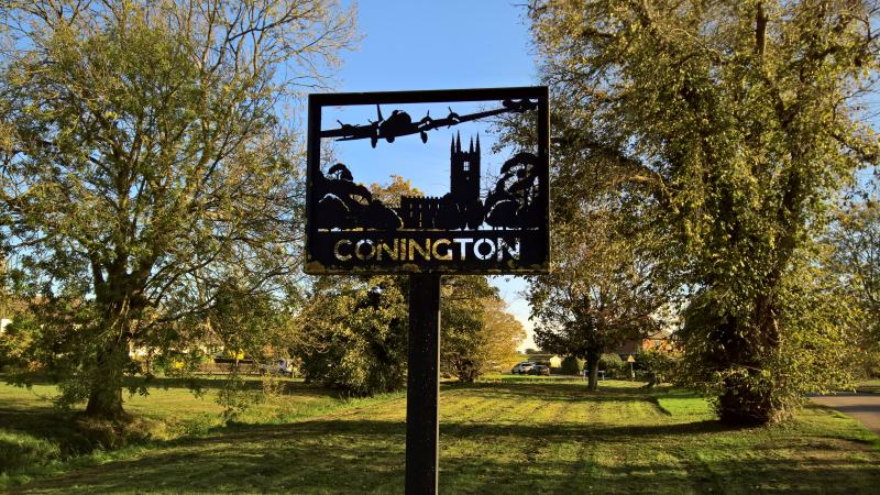 Village sign in Conington, with B-17 Flying Fortress commemorating the service of the 457th BG(H) at nearby Glatton airfield, Station 130.