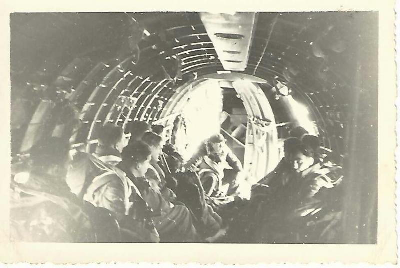 Staff Sergeant Ronald Roach of the 316th Troop Carrier Group, preparing to count British Paratroopers out of his aircraft during a mission over the Rhine, 1944.   Handwritten by Roach on the back:  '1944: Leading British Paratroopers to drop east of the Rhine. Roach in rear to count paratroopers as they jumped out.'