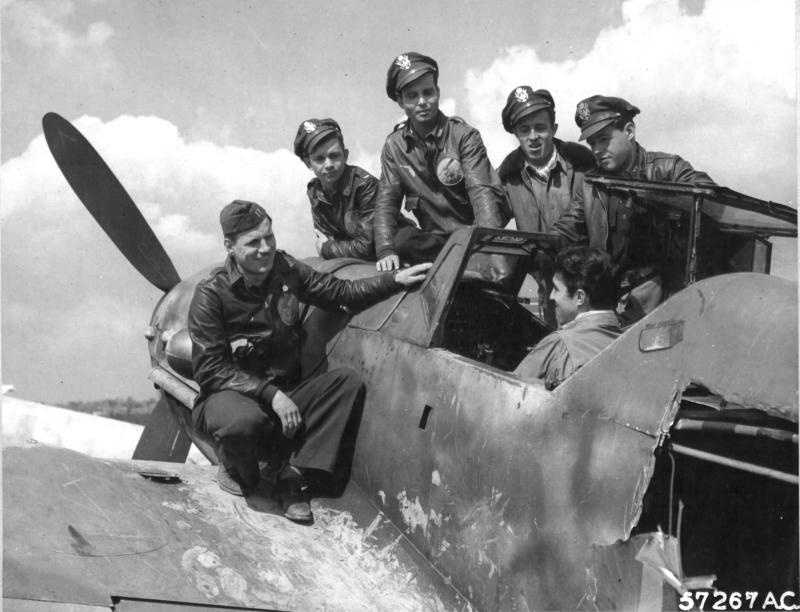 1st Lt. Robert C. Thoman, Rochester, NY, who recently shot down an Me-109, examines the cockpit of a similar enemy plane at a former Luftwaffe field as fellow 9th AF Republic P-47 Thunderbolt pilots look on. The pilots were given the opportunity to see at first hand many German aircraft which they have previously encountered in aerial combat or while strafing enemy fields when their group moved east of the Rhine to their second German airfield. 15 enemy planes of several types were found on the abandoned base.  L-R: Capt Paul A Van Cleef - Salina, KS, 1st Lt Thomas Manjak - Ambridge, PA, 1st Lt James L McWhorter - Sanford, FL, 2nd Lt Sherman E Price - Caplinger Mills, MO, 1st Lt John W Wise - Prosser, WA, 1st Lt. Robert C Thoman in cockpit. All are members of 365FG.