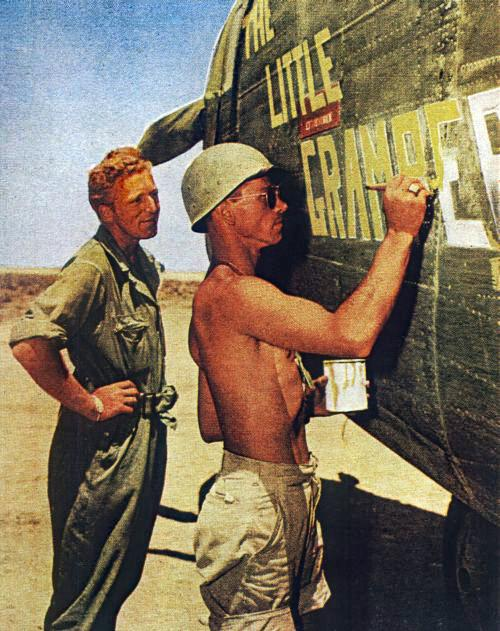 """T/Sgt.Arthur J. Marsh and S/Sgt.Charles Cavage of the 389th Bomb Group paint the nickname """"The Little Gramper"""