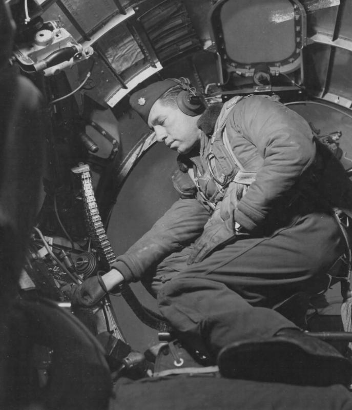 Major Charles S Hudson 91st Bomb Group in 'The Office' of a B-17 adjusts his equipment.