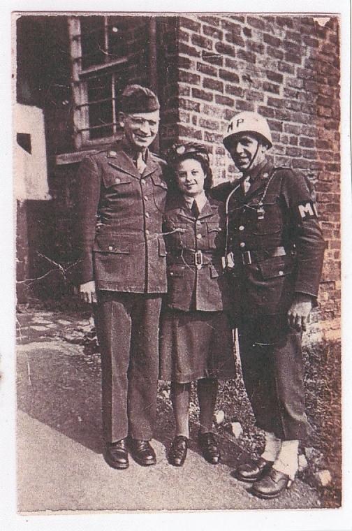 Edna Frost nee Emmett of the Women's Auxiliary Air Force with an American serviceman and Military Policeman at Headquarters of 9th Air Force Troop Carrier Command at St Vincents, Grantham.   According to her friend Eileen Pickering nee Gascoyne, Edna was fond of the Yanks. She later married Edward Frost, a night bomber with the RAF and together moved  to Canada.  Handwritten caption on reverse: 'Edna Emmett and 2  Yanks. No 5 Group Head Quarters 9th TCC.'