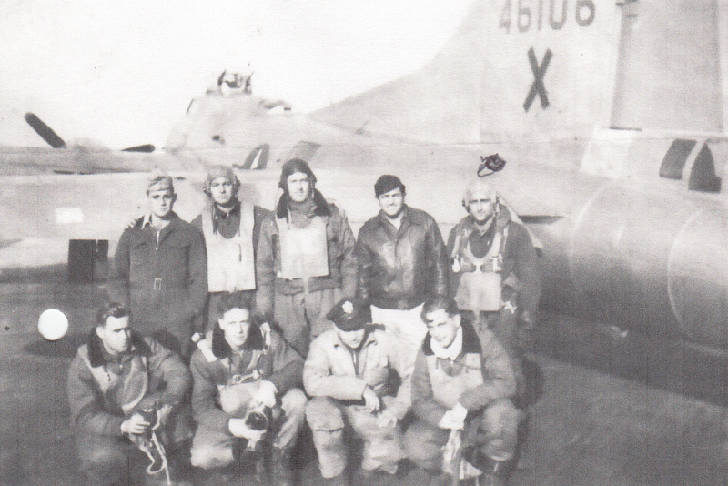 A bomber crew of the 388th Bomb Group with their B-17 Flying Fortress (serial number 44-6106). Segeant Charles A Alfano has been marked.   Printed caption: '388th Bomb Group Mousty Crew, Pilot- R B Mousty, Co-pilot- C Anker, Navigator- W Wohl, Radio Operator- R Ward, Radio Operator- GL Goupie, Engineer- JN Reddick, Bombardier- HL Wiersema, Waist Gunner- E G Christensen, Waist Gunner- JR Purcell, Tail Gunner- W Baker, Tail Gunner- CW Hall, Ball Turret- H Horowitz, Ball Turret- CA Alfano, Ball Turret- W Wood, Unknown- M Segrakous, Unknown- J Russell.'
