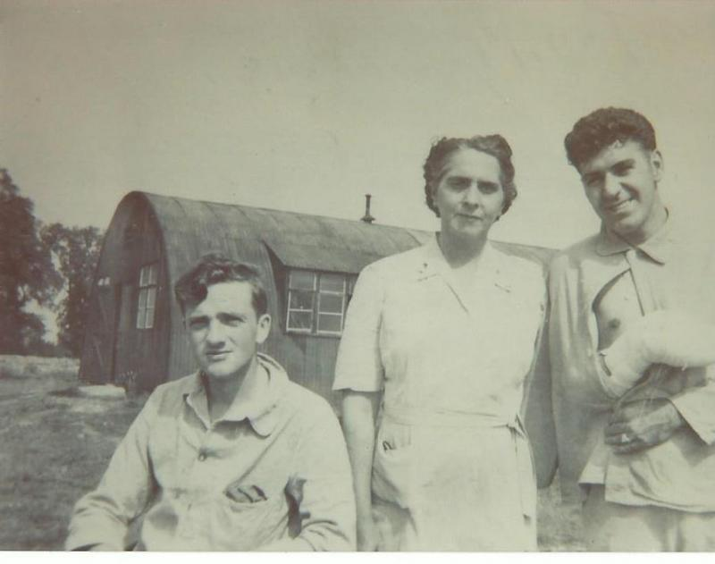 SSGT James O. Auman recuperating from being  wounded on the 9 August 1944 mission.  He was flying with Crew #421 - Eugene Godbout Crew as a replacement gunner that day instead of with his regular crew (Crew #431 - Robert H. Taylor Crew).  The nurse in the middle and the other recuperating patient are unknown.  It is known that the other wounded man was an armament specialist who had lost a thumb and part of his right hand loading bombs onto a B-24.  This may be at the 65th American General Hospital.