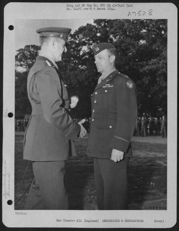 Lt. General  Jacob L. Devers congratulates Captain Frank S. Kamykowski of Montgomery,  Alabama after presenting him the Legion of Merit during a ceremony at Middlesex, England on 16 Octoober 1943.