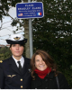 """Aspirant Amandine Alin, French apprentice-pilot and godmother of Lt Bradley B. Clark's grave at the Epinal American Cemetery and Cindy Clark, niece of Bradley, in front of the new sign placed near the crash place of P-47 Serial 42-28879 in Omelmont, France, 13 October 2013 (source : """"L'Est Républicain"""", 15 October 2013.)"""