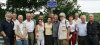 """20 July 2014 visit of Richard and Eve Clark to Omelmont. Richard is in the middle, between wife Eve (yellow blouse) and Jérôme Leclerc, secretary of the association Espace Mémoire Lorraine, surrounded by the team of volunteers in the Association. (source : """"L'est Républicain"""", 22 July 2014.)"""