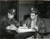 After Kassel, Sept. 27, 1944:   Lt. William Beyer (left), and Lt. Bocquin (right) prepare their reports.  While Bocquin downed three enemy planes, Beyer got five-- becoming an