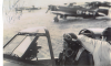 Ground Crewman Donald W Holdcraft of the 92nd Depot Repair Squadron straps Colonel Hubert A Zemke, commanding officer of the 56th Fighter Group into the cockpit of his P-47 Thunderbolt, 1944. Zemke has autographed the image and gifted it to Holdcraft.